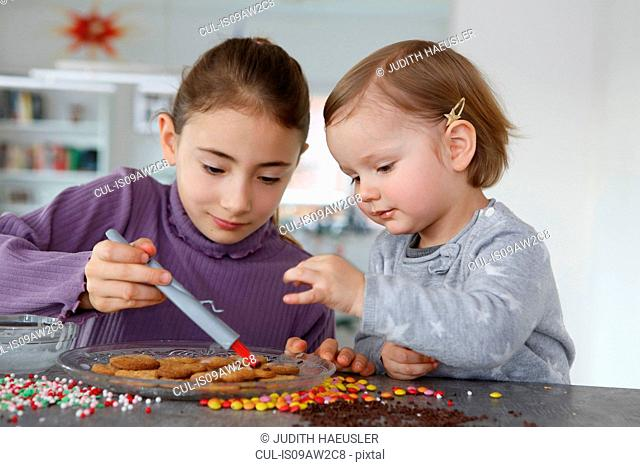 Girls at kitchen counter decorating cookies