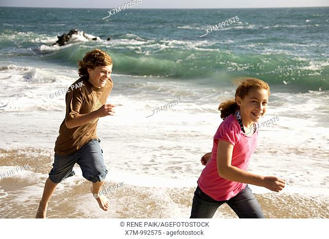 A caucasian boy playfully chases a young mixed race Mexican & caucasian girl on a beach in Santa Cruz, California