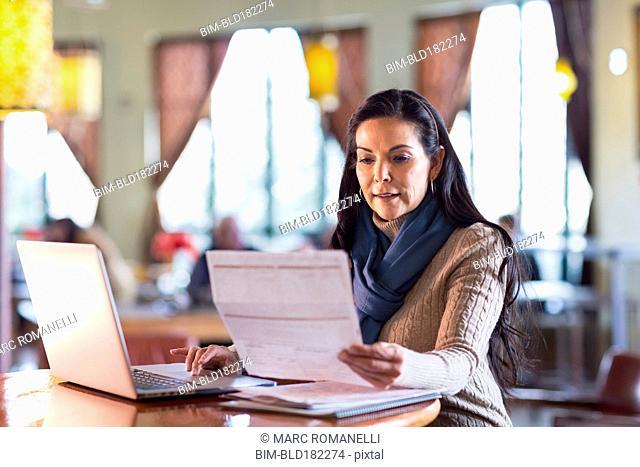 Hispanic woman paying bills on laptop in cafe