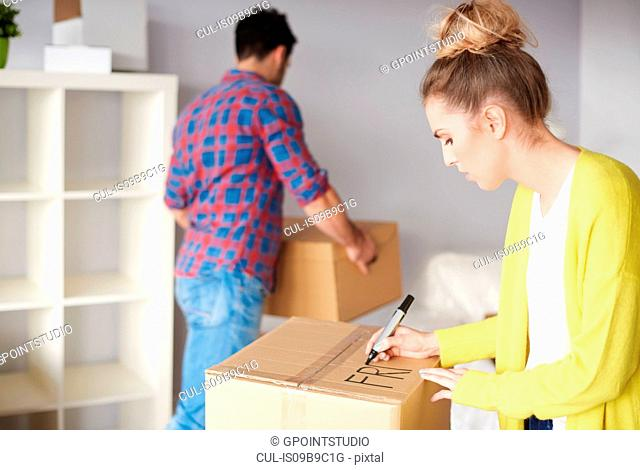 Young couple moving home, young woman labelling cardboard box