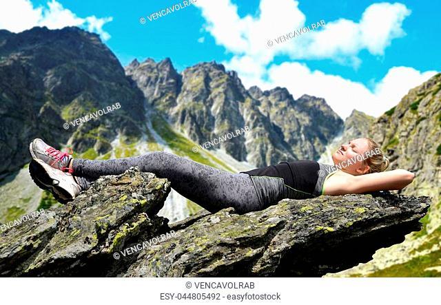 Tourist lying on a rock in Mengusovska Valley, Vysoke Tatry (High Tatras), Slovakia