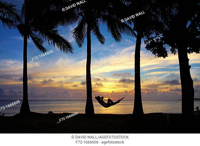 Woman in hammock, and palm trees at sunset, Coral Coast, Viti Levu, Fiji, South Pacific