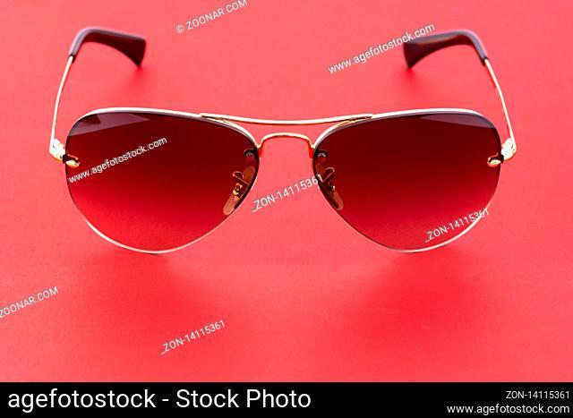 Studio shot of brown aviator sunglasses on red background
