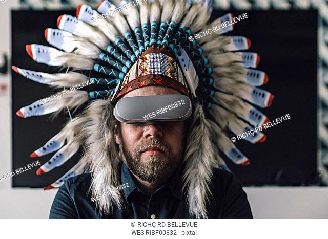 Man wearing Indian headdress and VR glasses in office