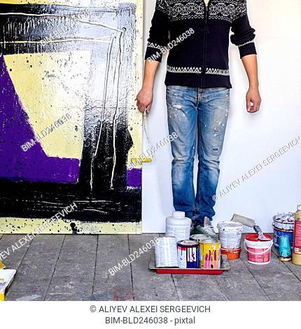 Caucasian artist holding paint roller near painting