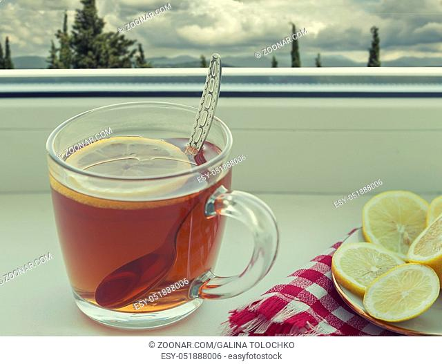 On the windowsill is a Cup of tea, next to the saucer lemon
