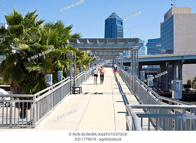 Joggers and walkers on the Northbank Riverwalk pedestrian bridge near the Fuller Warren Bridge in downtown Jacksonville, FL