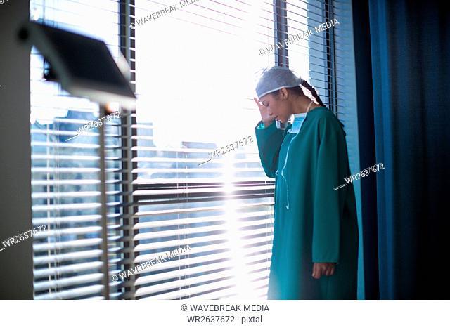 Tensed female surgeon standing near the window