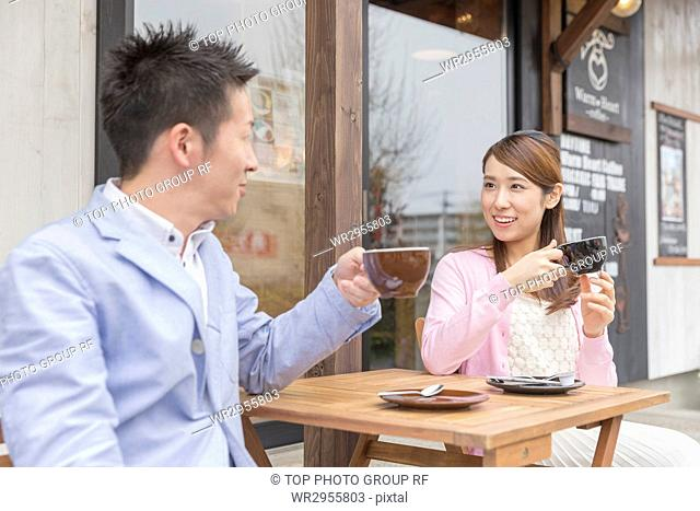 Couple Sitting in Chair and Having Coffee