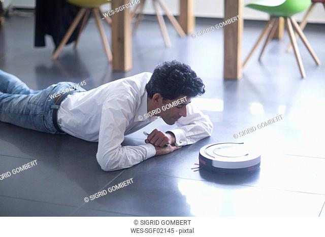 Man lying on the floor looking at robotic vacuum cleaner