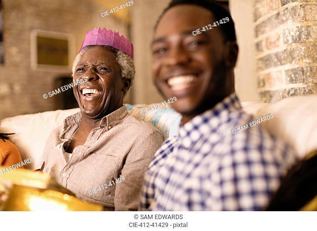 Laughing senior man wearing Christmas paper crown