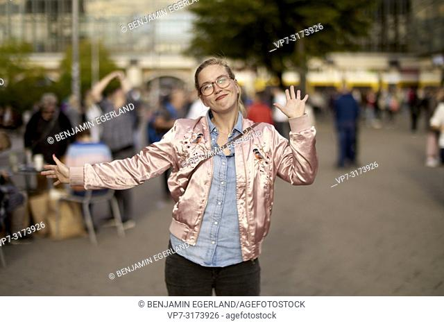 Lively woman with open arms dancing at Alexanderplatz, Berlin, Germany