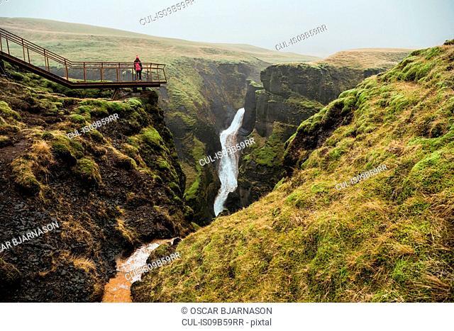 Tourist on footbridge looking out at canyon waterfall, Fjadrargljufur, Iceland