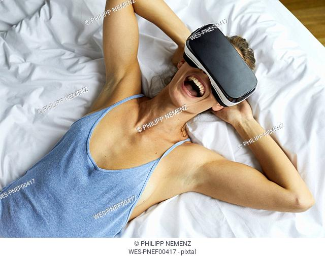 Laughing young woman lying in bed wearing VR glasses