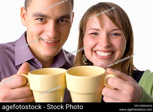 Happy couple holding cup next to cup. Isolated on white in studio