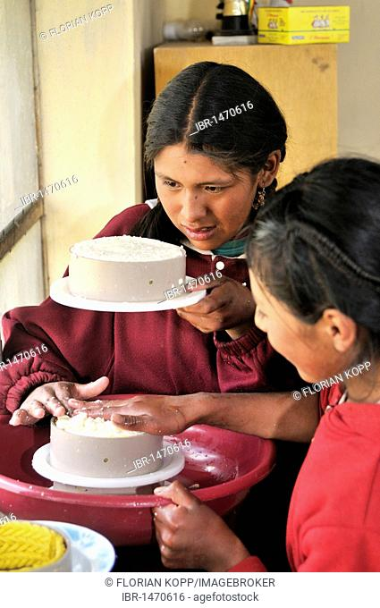 Production of fresh cheese in the Penas Valley, two young girls squeezing cheese into round shape, Departamento Oruro, Bolivia, South America