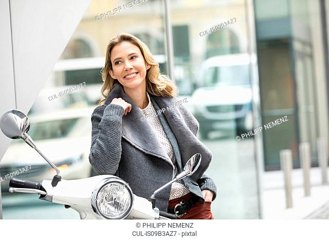 Mid adult woman leaning against moped on city street
