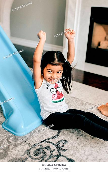 Girl with arms raised at bottom of slide in living room, portrait