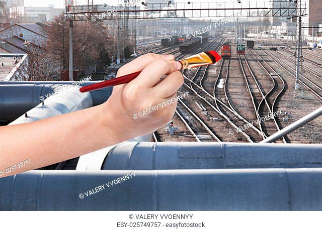 travel concept - hand with paintbrush paints red locomotive on railway station