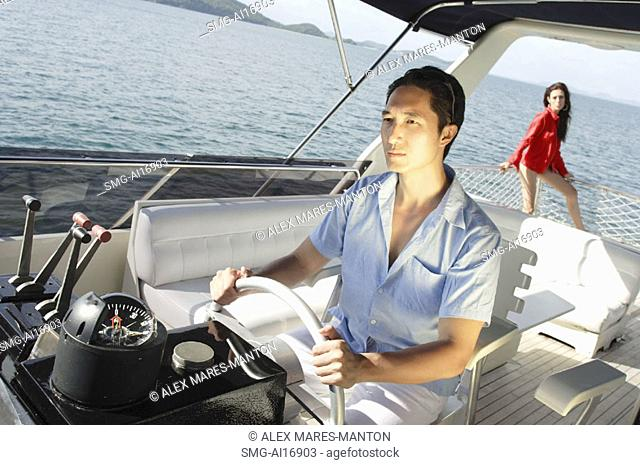 Man at helm of yacht, woman in the background