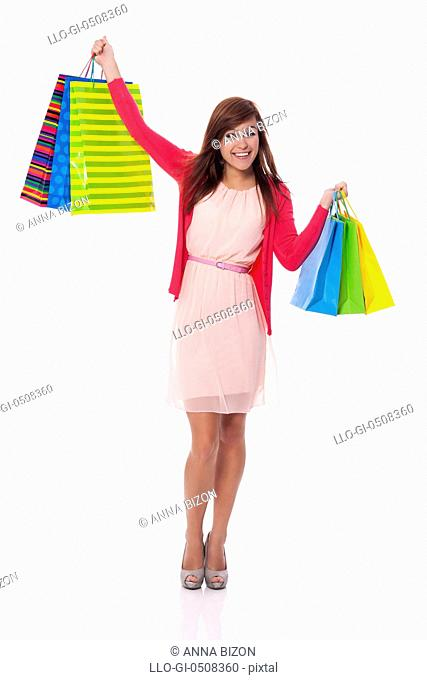 Smiling young woman holding up shopping bags Debica, Poland