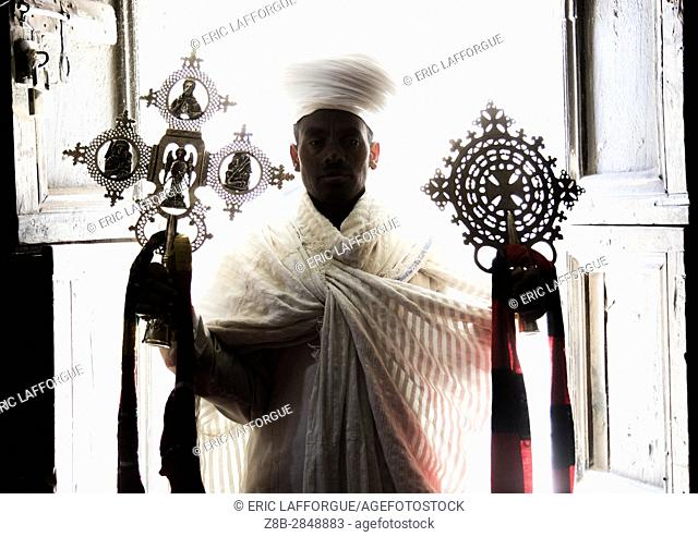 Portrait of an ethiopian orthodox priest holding crosses inside Asheten mariam rock hewn church, Amhara region, Lalibela, Ethiopia