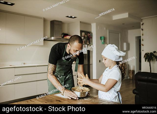 Father and daughter baking cookies at home