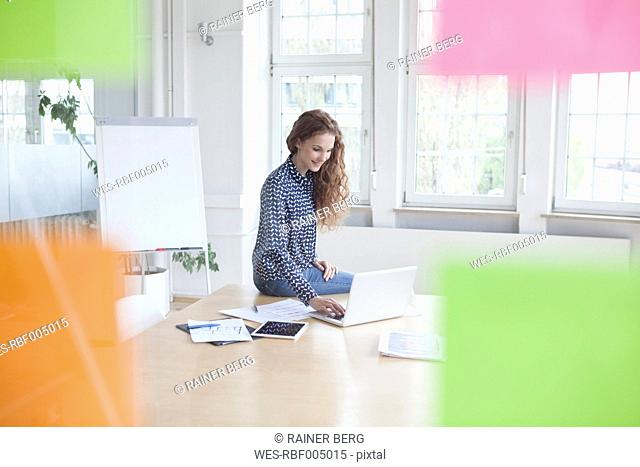 Woman using laptop in boardroom