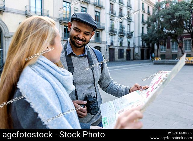 Happy couple with city map looking at each other, Barcelona, Spain