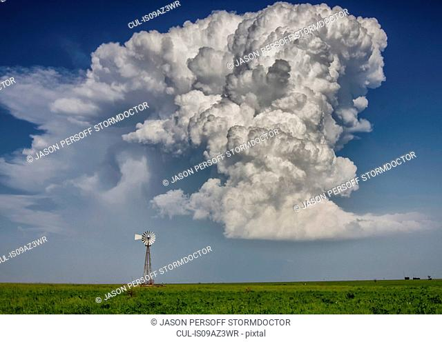 Supercell cloud over windmill on fertile plain