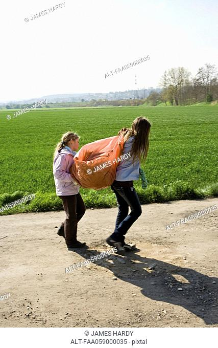 Girls carrying garbage bag together