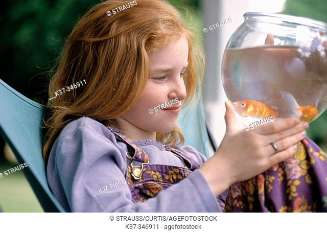 Young girl looking at gold fish in bowl