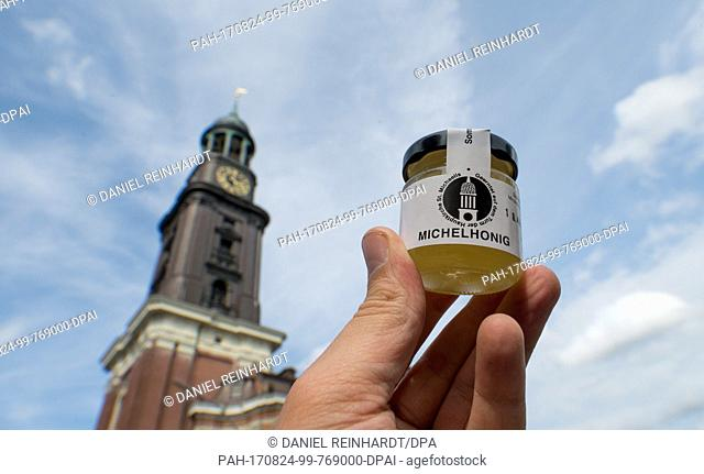 """A glass of """"""""Michaelhoney""""""""is standing in front of the St. Michael's Church in Hamburg, Germany, 24 August 2017. St. Michael's follows the example of the..."""