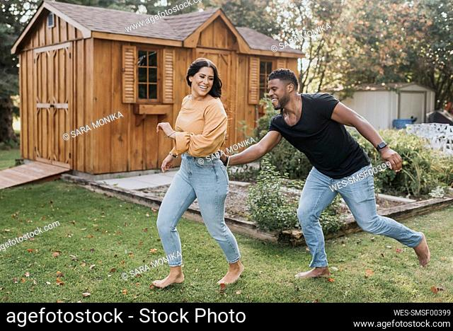 Man catching woman from behind while running at backyard