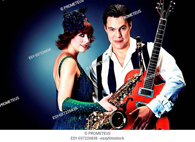 Couple of professional musicians in retro style posing in costumes at studio