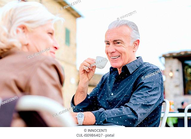 Over shoulder view of tourist couple drinking espresso at sidewalk cafe, Siena, Tuscany, Italy