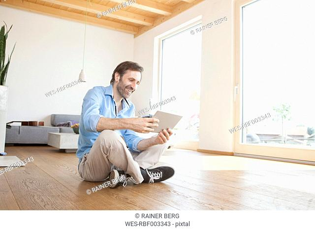 Mature man at home using digital tablet sitting on the floor
