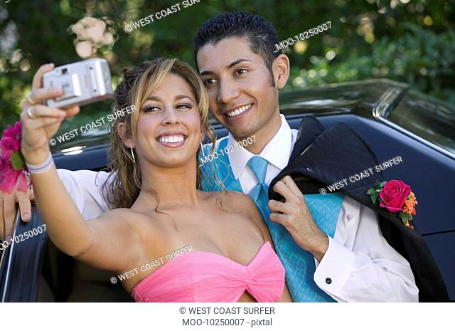 Well-dressed teenage couple taking picture outside car