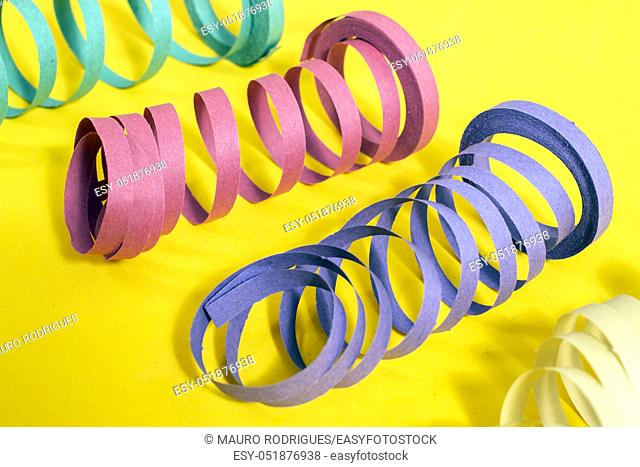 Mixed colorful streamers on a yellow background
