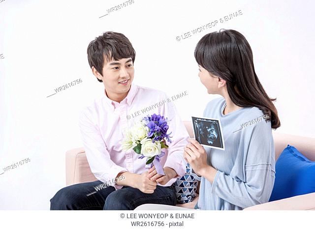 Young smiling couple with flowers and sonogram