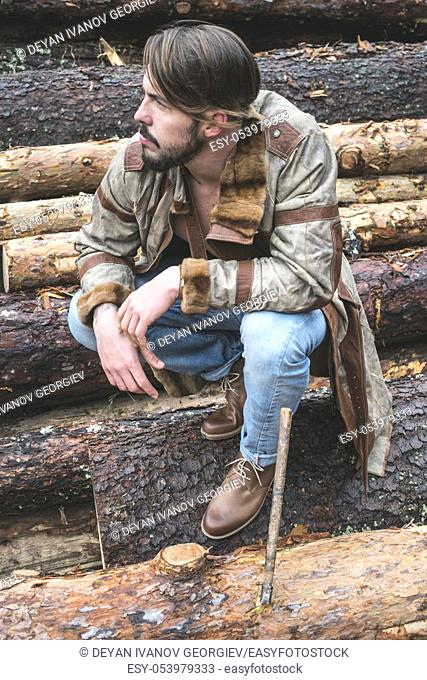 Young men on logs in the forest. Leather and jeans