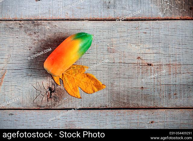 Papaya is ripe on old and dirty wooden floor