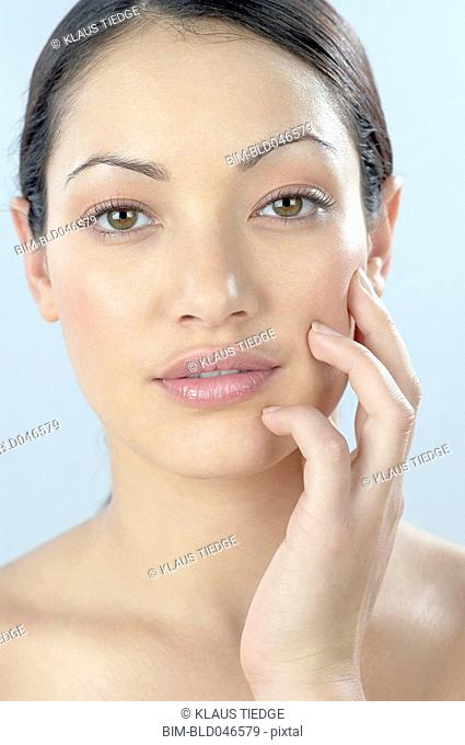 Mixed Race woman with hand on face