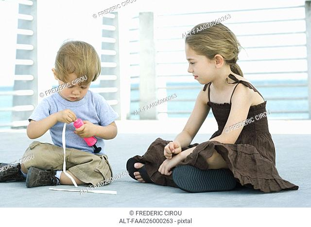 Little boy sitting on the ground inflating balloon with air pump, older sister watching