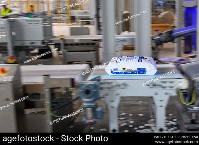 12 July 2021, Saxony-Anhalt, Staßfurt: A salt tablet produced and packaged at the new plant of the chemical company Ciech lies on a conveyor belt