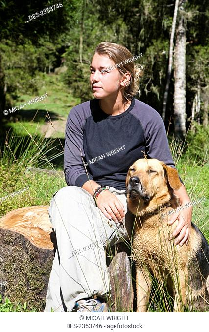 A Girl Sits Relaxing Outside On A Warm Summers Day With Her Dog At Blue Duck Lodge, In Whanganui National Park; Whakahoro, New Zealand