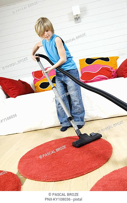 Young boy wit vacuum cleaner