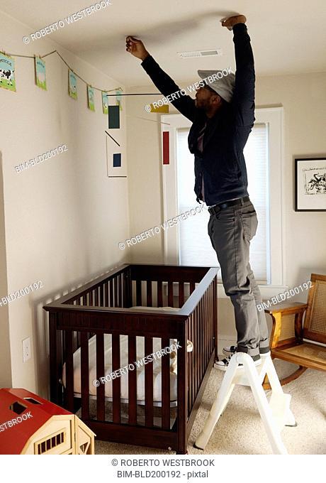 Black man decorating bedroom