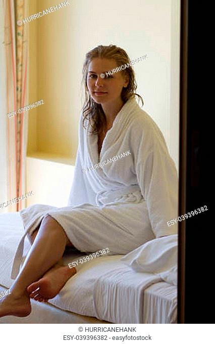 Attractive blond girl in white bathrobe relaxing after the bath at tourist resort