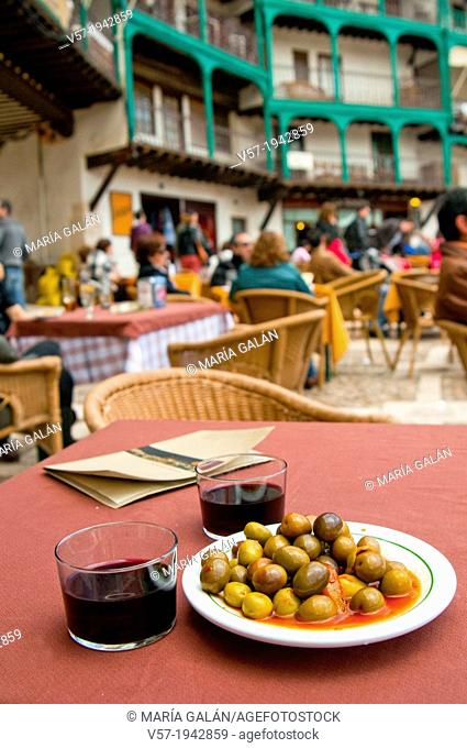 Spanish aperitif:olives with two glasses of red wine on a terrace. Main Square, Chinchon, Madrid province, Spain